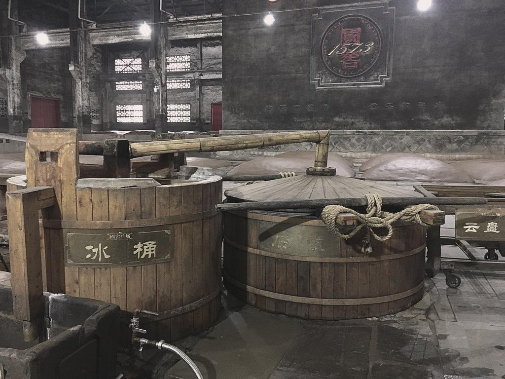 A traditional still in the Luzhou Laojiao distillery. In the back, there are the fermentation pits that have been operating non-stop since 1573. Source: Xiaomage de/Wikimedia